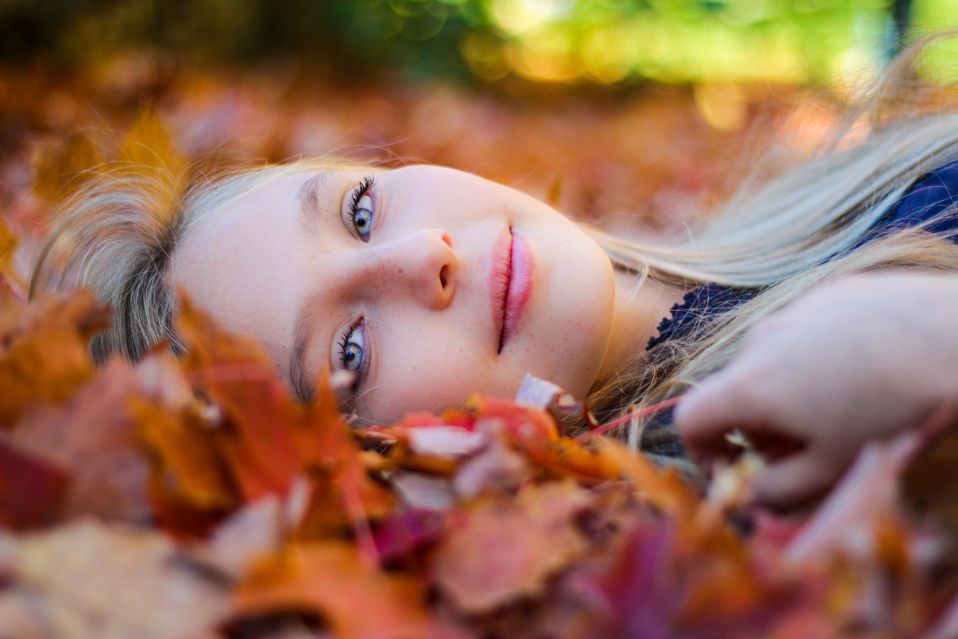 Person Lying On Ground Among Autumnal Leaves, Healthy Skin