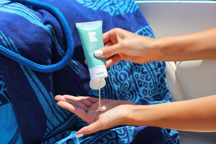 closeup of person squeezing sunscreen from tube into hand, next to blue clothing