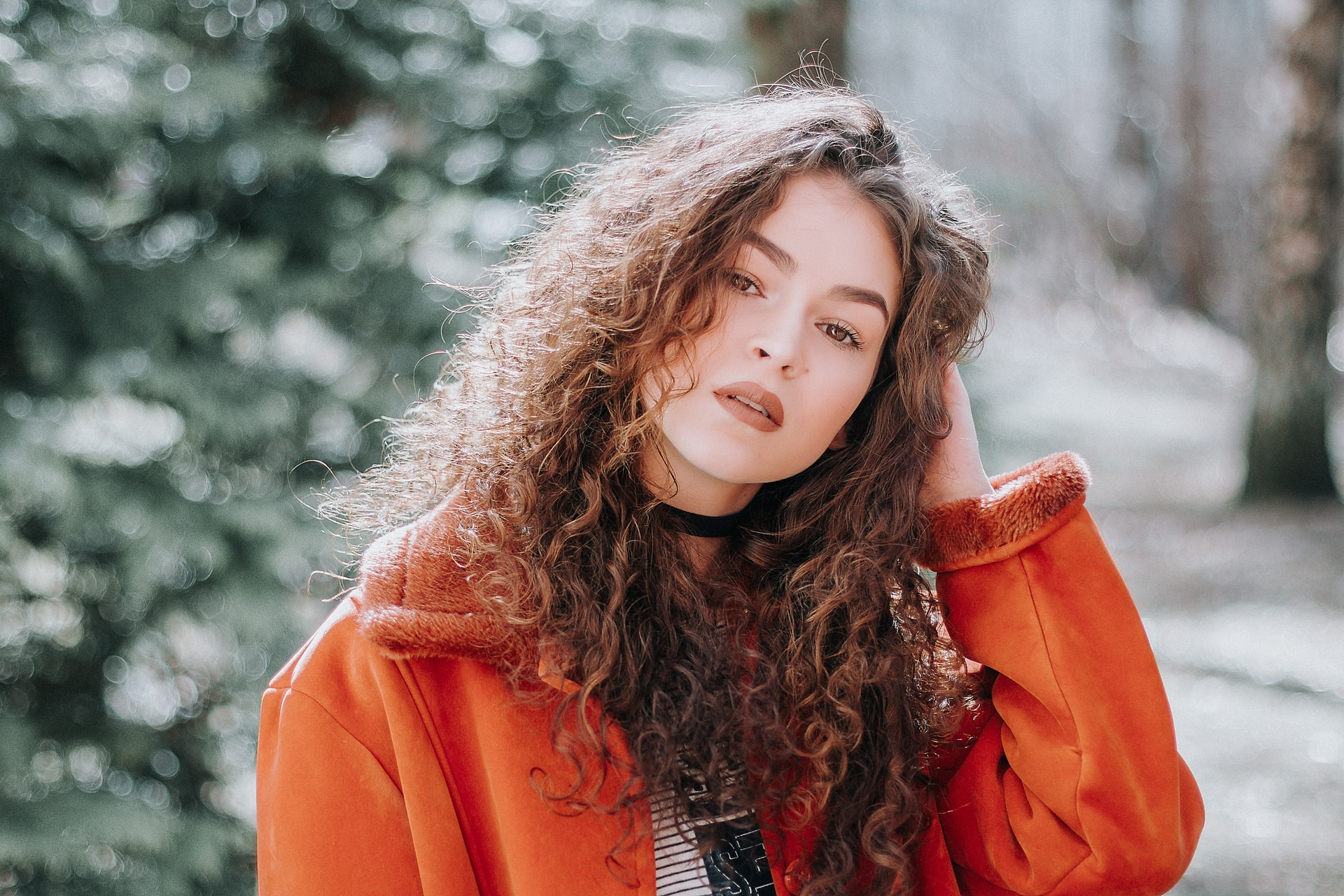 Person With Curly Hair Faces Camera, Hand On Back Of Head, Against Wintery Background
