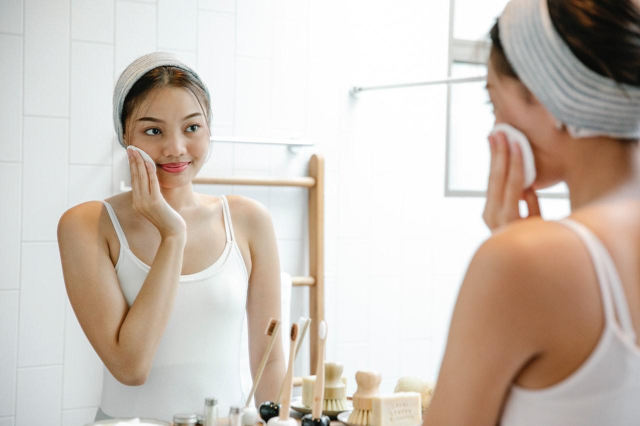 Person Doing Skincare In Mirror, Should You Skip Retinol When It's Sunny