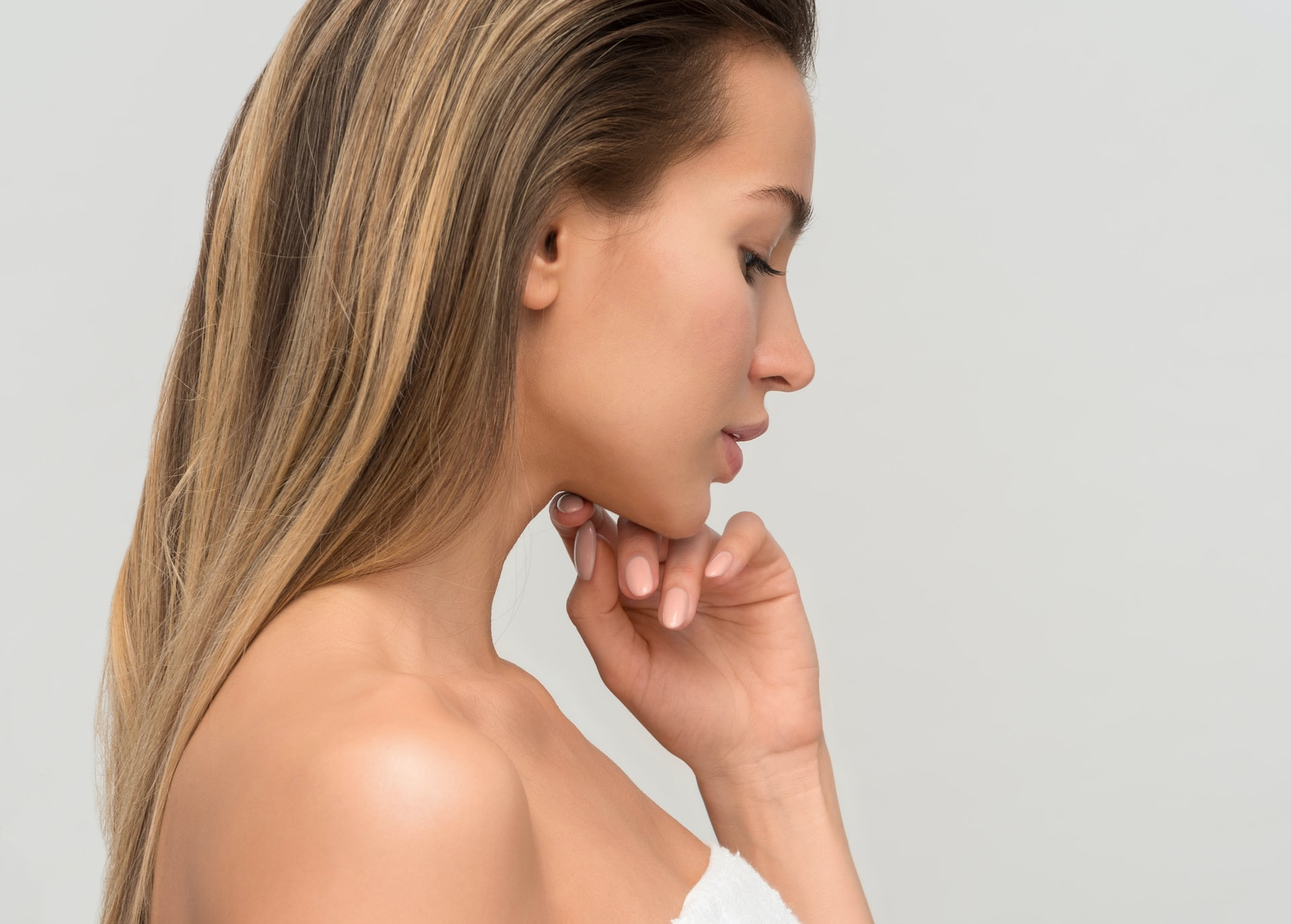 Model With Healthy Skin Poses Side-on, Hand Under Chin, Thinking About Ceramides