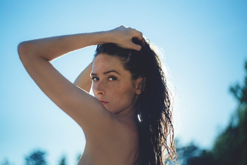 woman looks to camera, hands on head, sun behind her